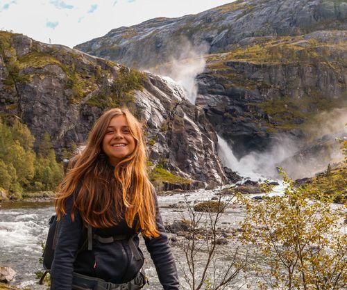 Mujer muy contenta con la cascada Sotefossen de fondo