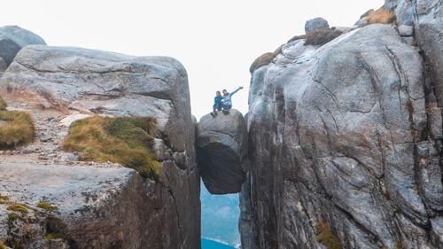 Roca flotante de Kjeragbolten con gente sentada encima
