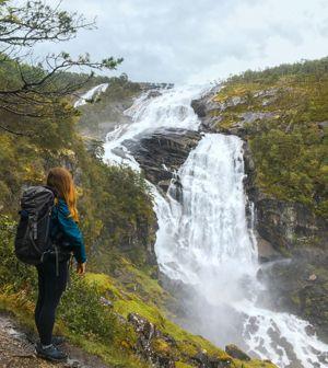 Persona observando la enorme cascada en Husedalen