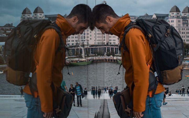 Joven apoyando la cabeza a la pared de cristal de la Opera de Oslo