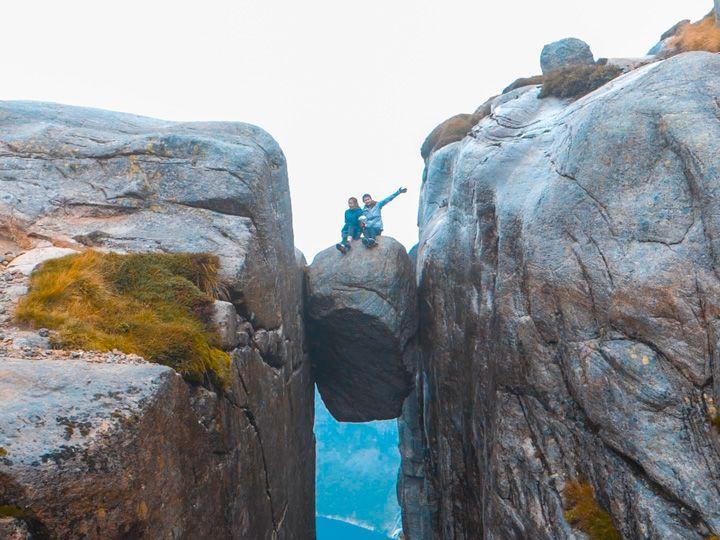 Roca de Kjeragbolten con dos personas sentadas encima