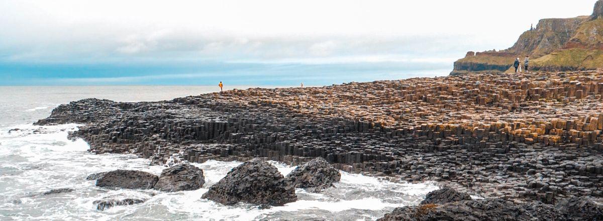 Panorámica de Giant's Causeway con el agua golpeando sus columnas