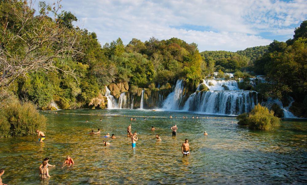 Lago con gente bañándose y con Skradin Buk de fondo en el parque nacional Krka