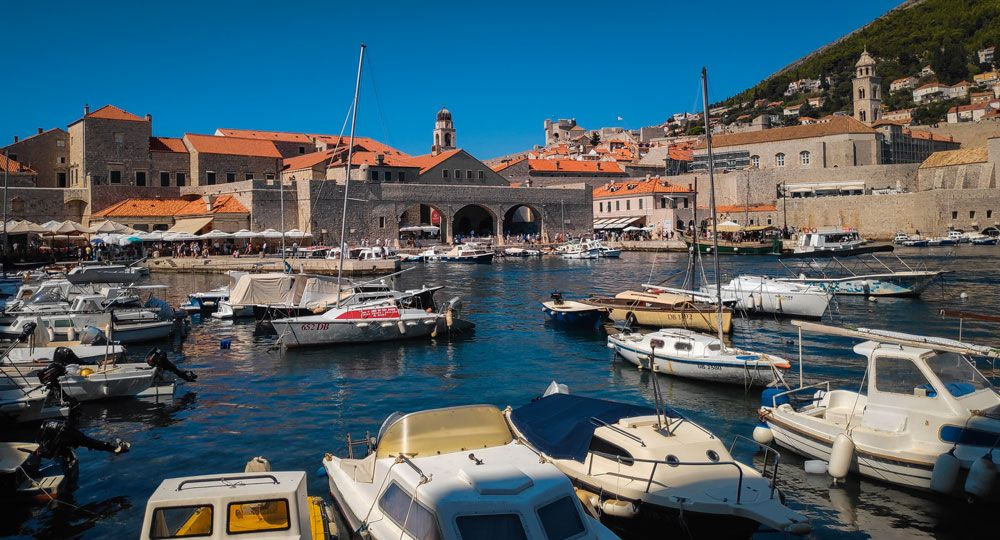Barcas atracadas en el puerto de Dubrovnik protegido por las murallas