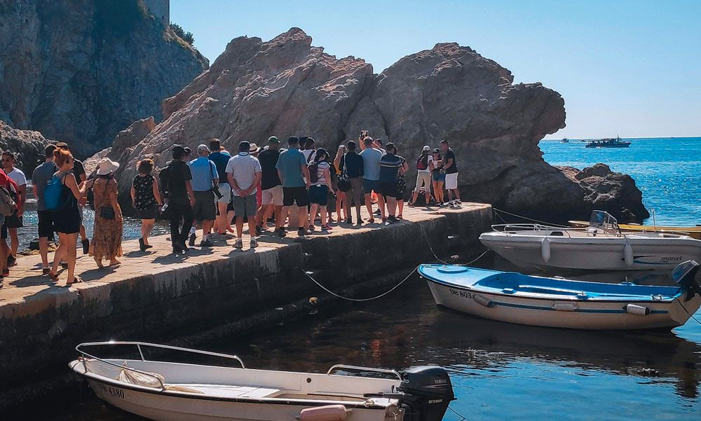 Embarcadero de la bahía de Dubrovnik lleno de gente con algunas barcas